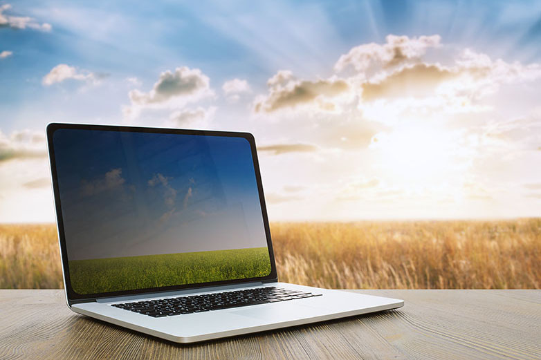 Laptop on table with grassy field and a blue cloudy sky in background