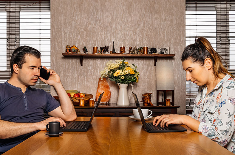 Couple both working from home on their laptops at the kitchen table