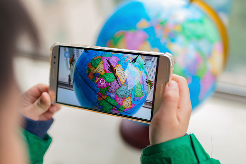 Child plays online game with a globe