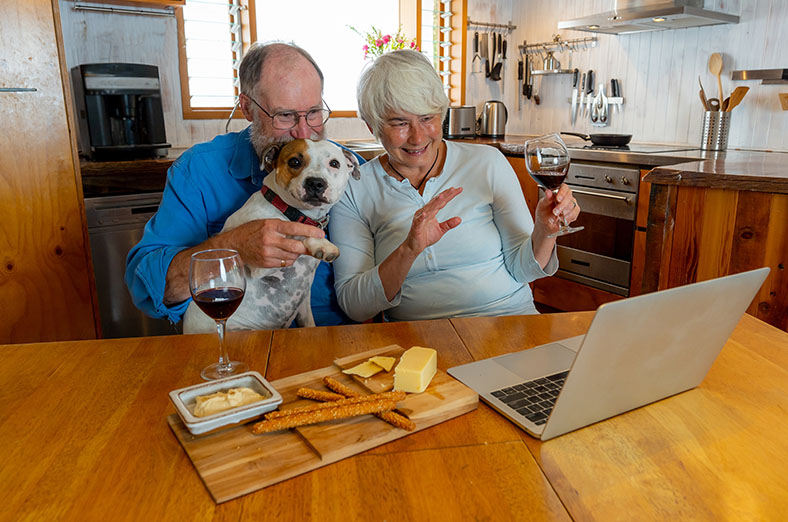 Senior couple having drinks and nibbles on the internet with their dog