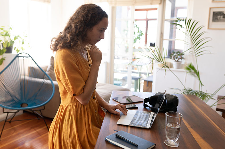 Young trendy woman at home with her laptop