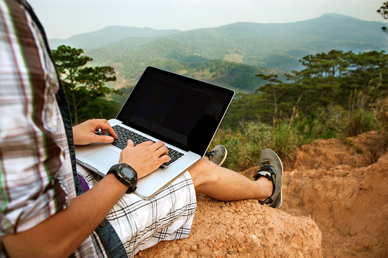 Man works remotely with a country view