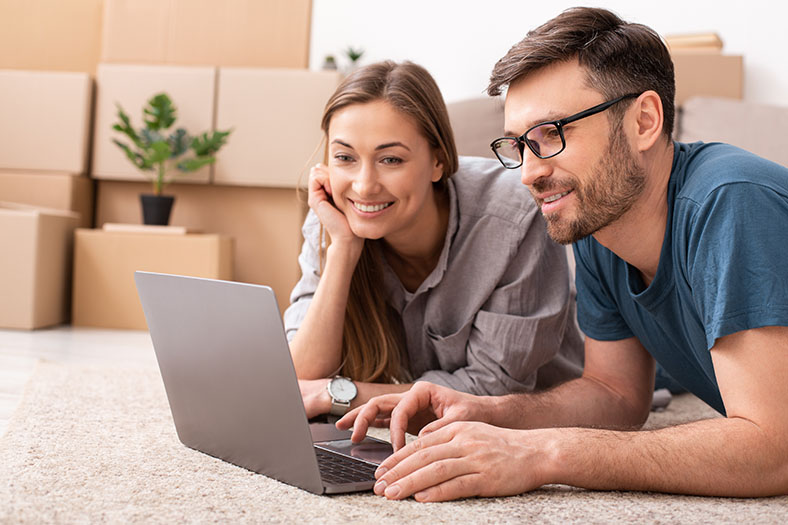 Young couple surrounded by moving boxes, lay on the floor with laptop