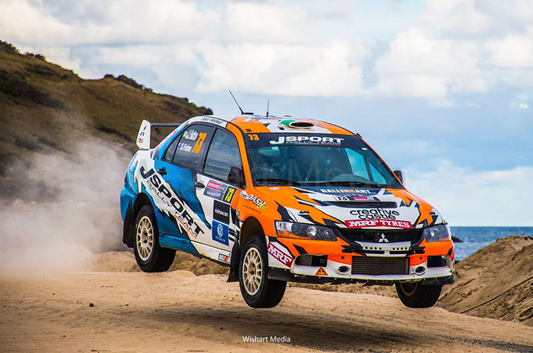 Wishart Media image of an orange and blue rally car in flight along a dirt track