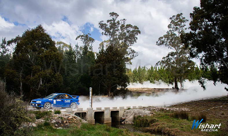 Blue rally car racing down the bush track leaving dust behind it