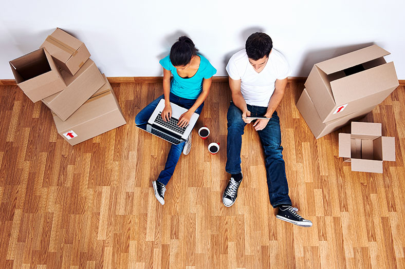 Young couple use internet surrounded by moving boxes