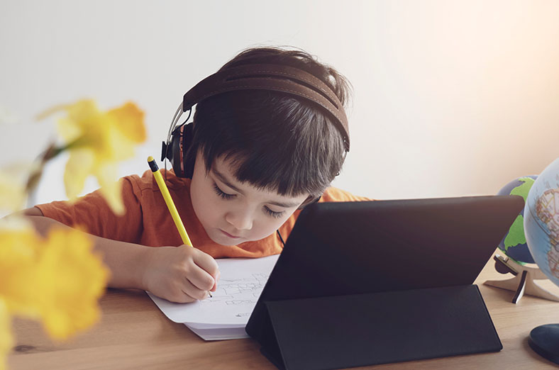 Little boys uses tablet for distance education