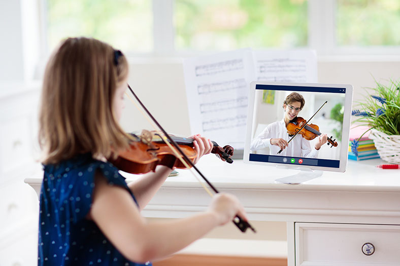 Girl learns violin on the computer