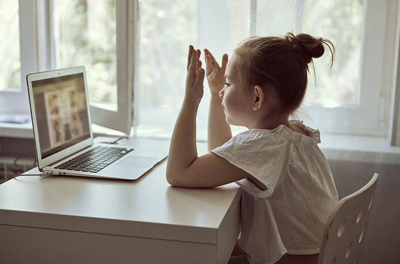 Little girl using a laptop for distance education