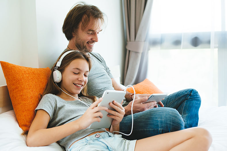 Happy father and daughter using the internet