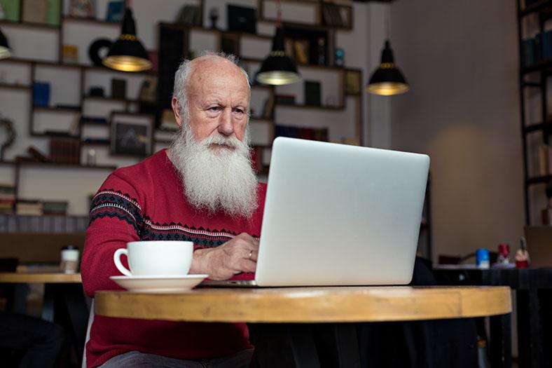 Santa lookalike uses laptop