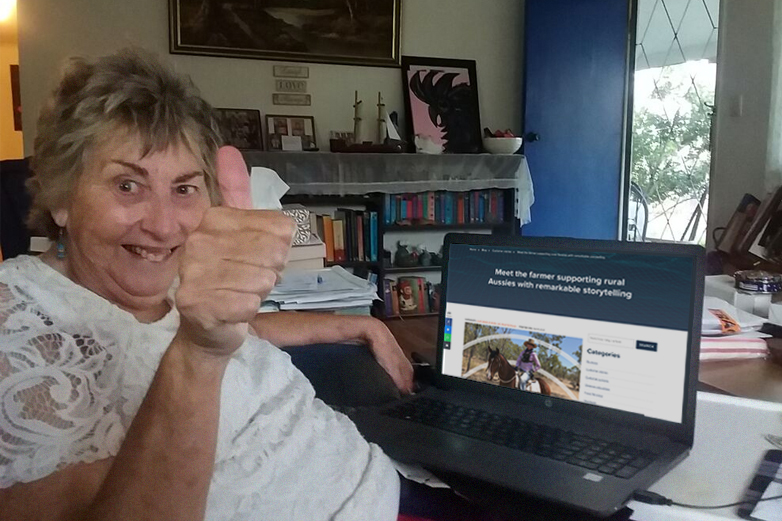Older rural woman who is one of SkyMesh's customers sits at her laptop looking at the SkyMesh blog and giving the thumbs up with a smile on her face.
