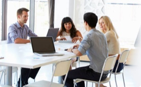 A small group of four people sat at a desk in conversation